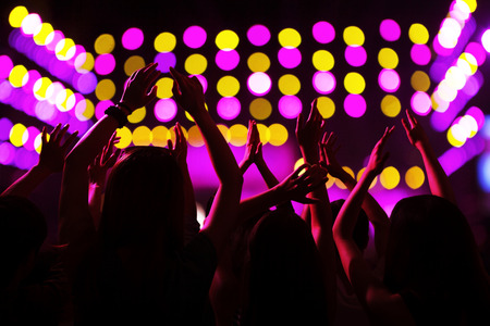 above 18: Audience watching a rock show, hands in the air, rear view, stage lights Stock Photo