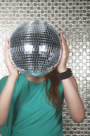 above 18: Young woman holding a disco ball in front of her face
