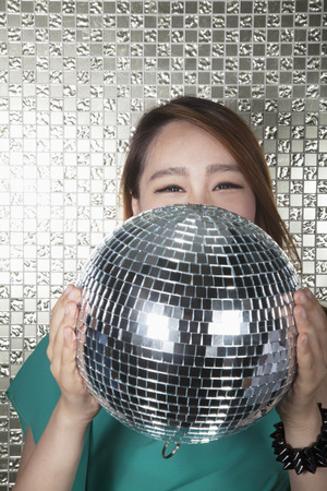 above 18: Young woman holding a disco ball, looking at camera in front of shiny wall Stock Photo