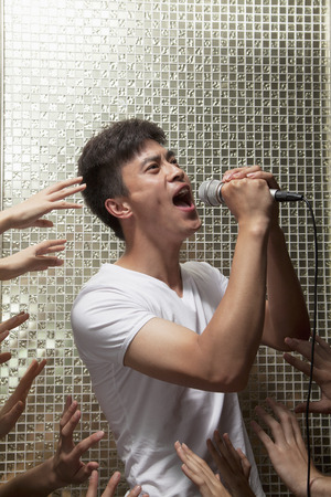 above 18: Young man singing into a microphone with lots of hands reaching for him Stock Photo