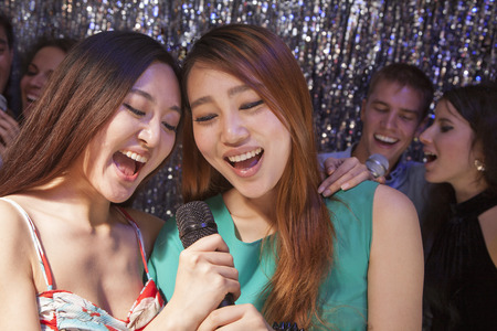 above 18: Group of friends singing into a microphone at karaoke