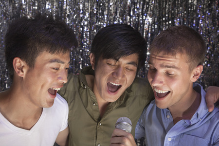 above 21: Three friends with arm around each other holding a microphone and singing together at karaoke