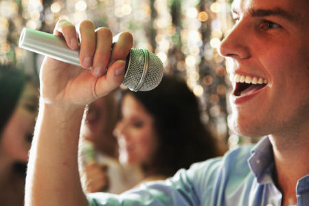karaoke: Close- up of young man holding a microphone and singing at karaoke, friends singing in the background Stock Photo