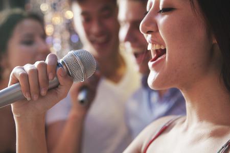 gente cantando: Cerrar-up de la mujer joven que sostiene un micr�fono y cantando en el karaoke, amigos cantando en el fondo