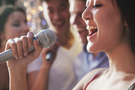 singing: Close- up of young woman holding a microphone and singing at karaoke, friends singing in the background