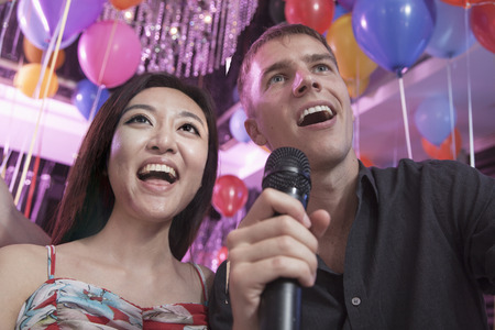 above 21: Two friends singing into a microphone together in a nightclub for karaoke