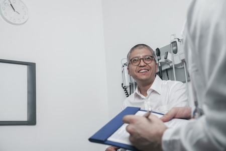 Doctor writing on medical chart with a smiling patient photo