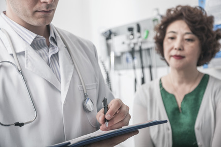 chinese women: Doctor writing on medical chart with patient in the background