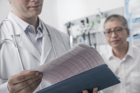 Doctor checking medical chart with patient in the background photo