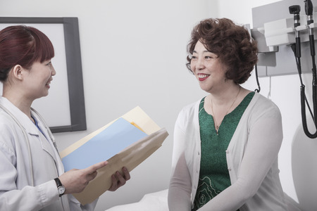 Smiling doctor holding a medical chart and consulting with a patient
