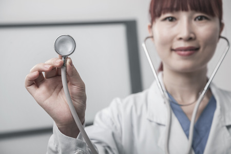 Portrait of female doctor holding a stethoscope Imagens