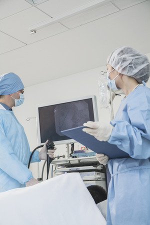 Two surgeons preparing for surgery, patient lying down photo