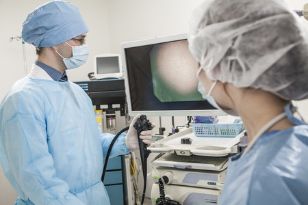 Two surgeons preparing for surgery, looking at medical equipment photo