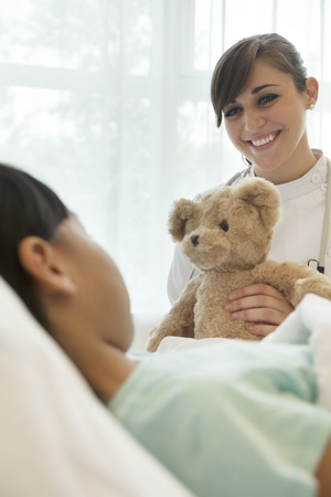 some under 18: Smiling female doctor giving a teddy bear to a girl patient lying down on a hospital bed