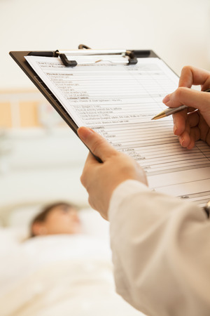 Close up of doctor writing on a medical chart with patient lying in a hospital bed in the background photo
