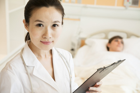 Portrait of smiling doctor holding a medical chart with patient lying in a hospital bed in the background photo
