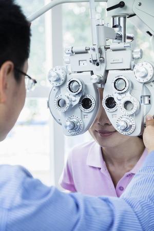 Optometrist doing an eye exam on young woman photo