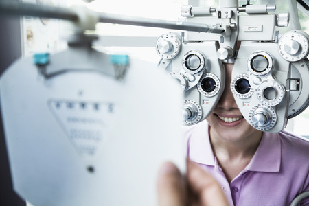 above 25: Close-up of optometrist doing an eye exam on young woman