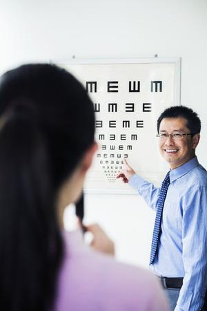 eye chart: Optometrist administering an eye exam on a eye chart