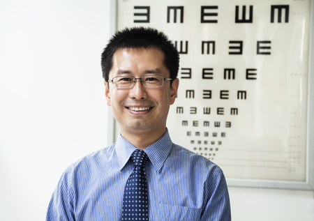 above 30: Portrait of smiling optometrist with an eye chart in the background