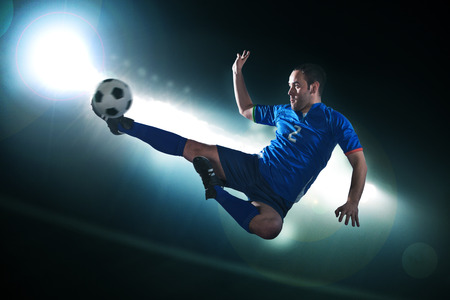 expertise: Soccer player in mid air kicking the soccer ball, stadium lights at night in background Stock Photo
