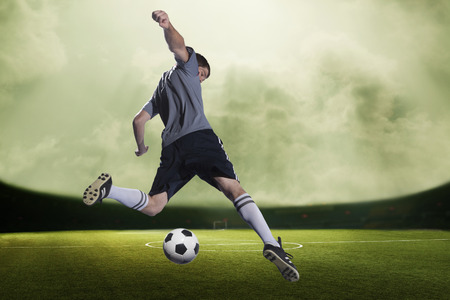 kicking ball: Soccer player kicking the ball in a stadium, green sky with clouds