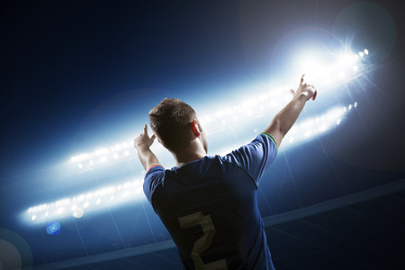 Soccer player with arms raised cheering, stadium at night time