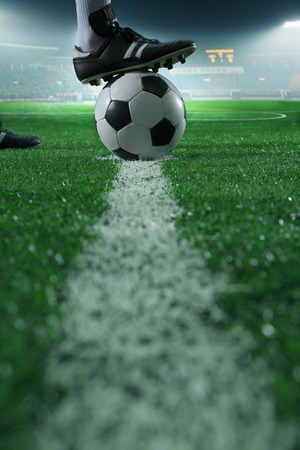 kicking ball: Close up of foot on top of soccer ball on the line, side view, stadium