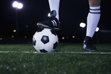 level playing field: Close up of feet on top of soccer ball on the line, night time in the stadium