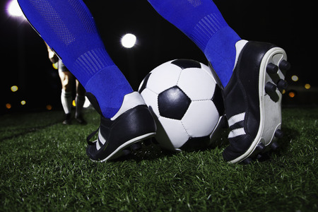 Close up of feet kicking the soccer ball, night time in the stadium photo