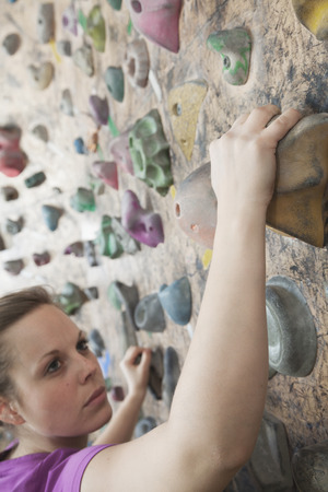 recreational climbing: Determined young woman climbing up a climbing wall in an indoor climbing gym