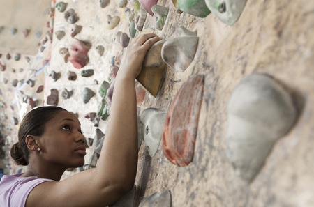grabbing at the back: Determined young woman climbing up a climbing wall in an indoor climbing gym