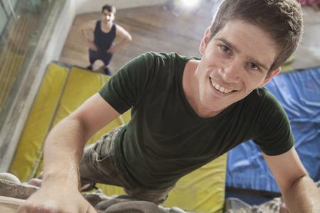 climbing  wall: Close-up of smiling young man climbing up a climbing wall in an indoor climbing gym