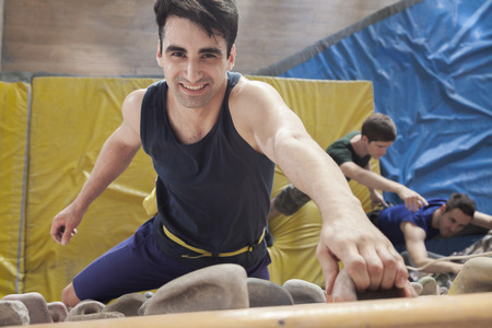 directly above: Smiling young man climbing up a climbing wall in an indoor climbing gym, directly above