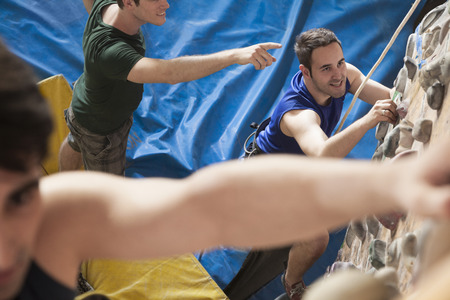 climbing wall: Three young men point and climbing in an indoor climbing gym