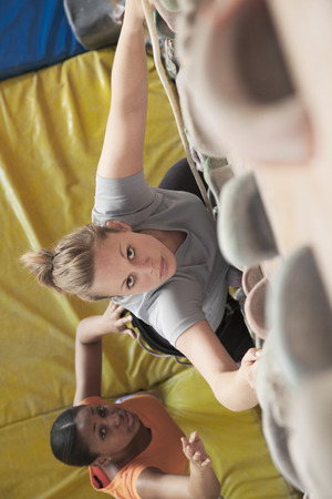 climbing wall: Two young women climbing in an indoor climbing gym, directly above