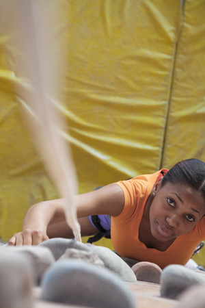 grabbing back: Determined young woman climbing up a climbing wall in an indoor climbing gym, directly above Stock Photo