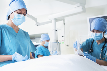 above 18: Team of surgeons working with a patient lying on the operating table Stock Photo