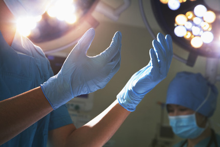 Midsection view of hands in surgical gloves and surgical lights in the operating room
