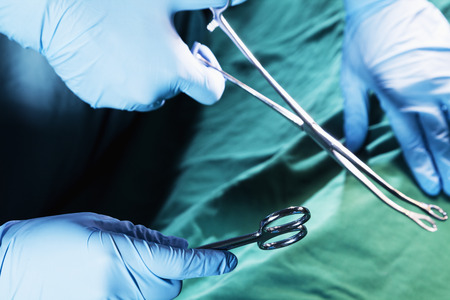 Close-up of gloved hands holding the surgical scissors and working, operating room, hospital photo