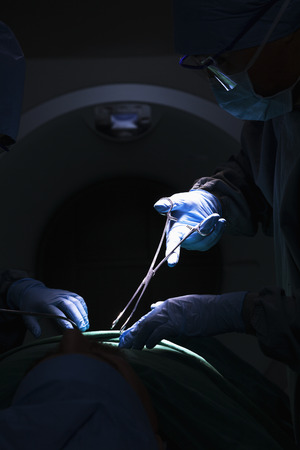 Surgeon looking down, working, and holding surgical equipment with patient lying on the operating table, dark photo