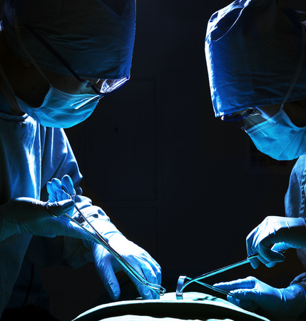 Two surgeons looking down, working, and holding surgical equipment with patient lying on the operating table