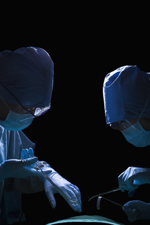 Two surgeons looking down, working, and holding surgical equipment with patient lying on the operating table  photo