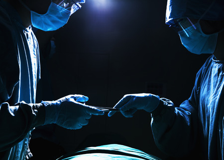 surgical equipment: Two surgeons working and passing surgical equipment in the operating room, dark