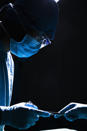 surgical equipment: Two surgeons working and passing surgical equipment in the operating room, dark, close-up