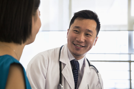 above 18: Smiling doctor sitting down and consulting patient in the hospital, close-up