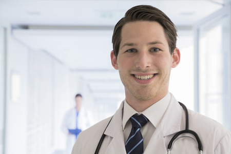 bata de laboratorio: Portrait of young doctor in lab coat in the hospital, looking at camera, close-up Foto de archivo