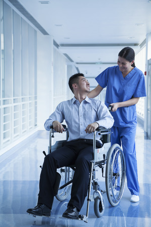 above 30: Smiling female nurse pushing and assisting patient in a wheelchair in the hospital  Stock Photo