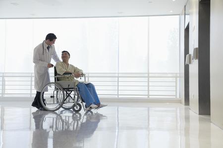 Doctor duwen en assisteren de patiënt in het ziekenhuis, Beijing, China