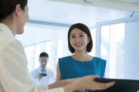 above 18: Smiling doctor and patient standing by the counter in the hospital looking down at medical record